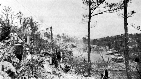 YUZA PEAK, under attack by the 382d Infantry, 96th Division. Tanks are working on the caves and tunnel system at base ridge of ridge.