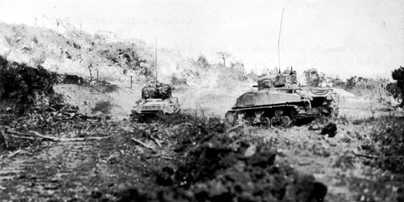 FIGHTING TOWARD HILL 89, tanks of the 769th Tank Battalion attack a bypassed Japanese strong point on top of Yaeju-Dake, 18 June 1945