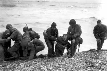 Photo, Members of an American landing party lend helping hands to other members of their organization whose landing craft was sunk be enemy action of the coast of France, Omaha  Beach, 6 June 1944