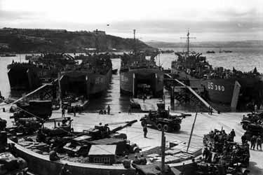Photo, In preparation for the invasion, artillery equipment is loaded aboard LCTS at an English port. Brixham, England. 1 June 1944