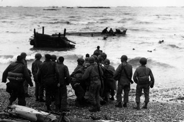 Photo, GIs who have landed on the northern coast of France during the early stages of D-Day man a life line to help other Americans approaching the beach