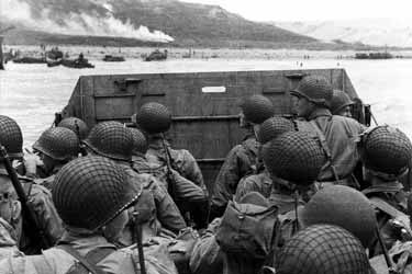 Photo, American assault troops in a landing craft huddle behind the protective front of the craft as it nears a beachhead, on the Northern Coast of France, 6 June 1944