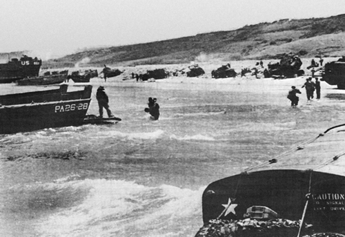Photo:  Tanks and vehicles stalled at the shingle line on OMAHA Beach
