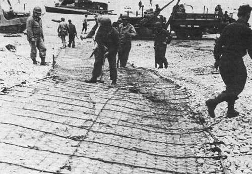Photo:  Engineers anchor reinforced track for vehicles coming ashore at OMAHA