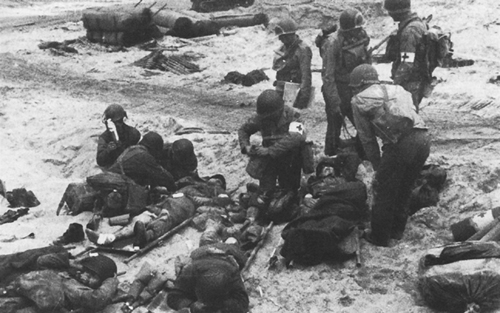 Photo:  Medics administering first aid to invasion casualties on UTAH Beach
