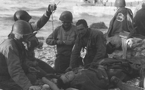 Photo:  Medics administering first aid to invasion casualties on OMAHA Beach