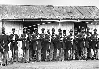 The 107th U.S. Colored Infantry served in Virginia and North Carolina before spending its last year, 1865�1866, guarding ordnance stores and other public property around Washington, D.C. In this cracked image, men of the regiment form in front of the guardhouse at Fort Corcoran, across the Potomac from Georgetown.